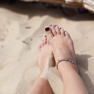 Two bare feet partly in the sand with toenails painted deep red and the right foot is wearing an ankle bracelet jewellery and there is a log in the background| Simple Summer Self Care | Passion by Kait