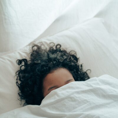 the top of a person's head with black curly hair appears from a white sheet and they are lying on a white pillow in a bed | How To Increase You're LIbido When You're Too Tired | Passion by Kait