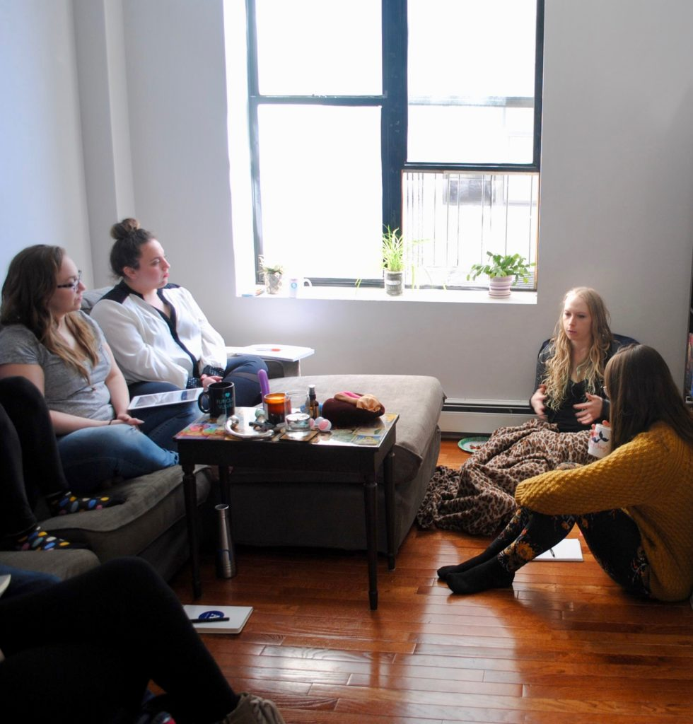 Our founder, Kait, teaching one of our sex class in NYC. A group of femmes are sitting in a circle around an altar. | Sex Classes NYC and Beyond - Passion by Kait