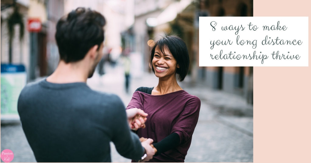 A couple faces each other, smiling and holding hands. | How to Make Your Long Distance Relationship Work | Passion by Kait