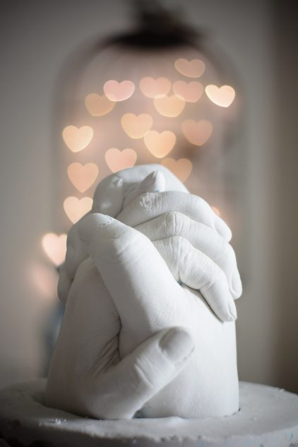 Alabaster sclupture of clasped hands with hanging heart-shaped lights in the background |Male Sexual Desire is More Complex than You Think | Passion by Kait