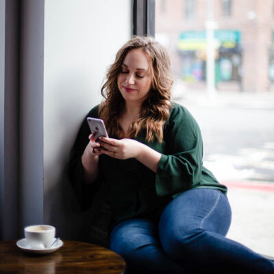 Kait sits in a window seat looking at her phone. Since going off birth control, she tracks her sex dirve and other cycle indicators with the Clue app. | How my sex drive changed after birth control