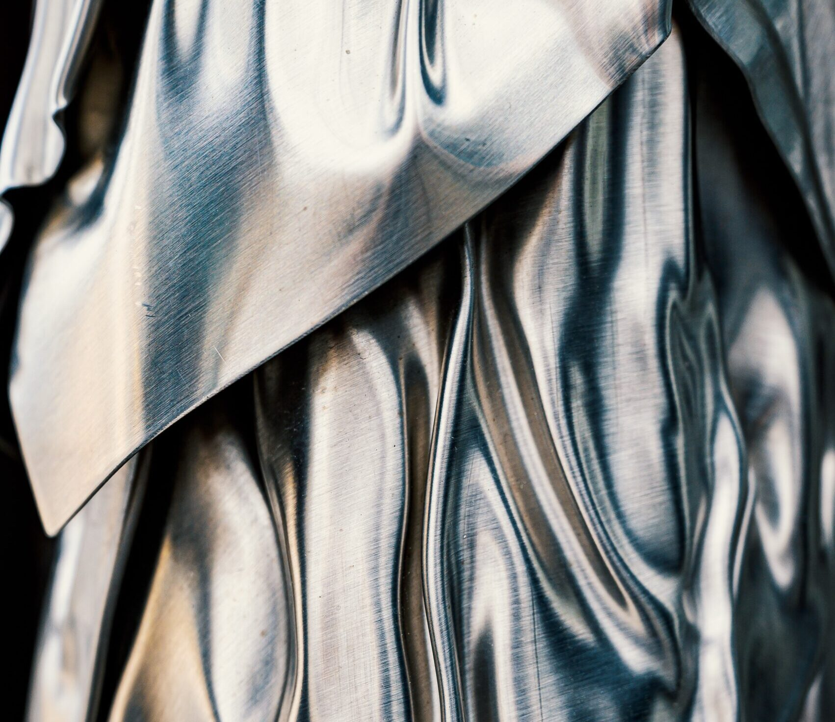 silver grey shiny silky sheet with many folds and creases in it