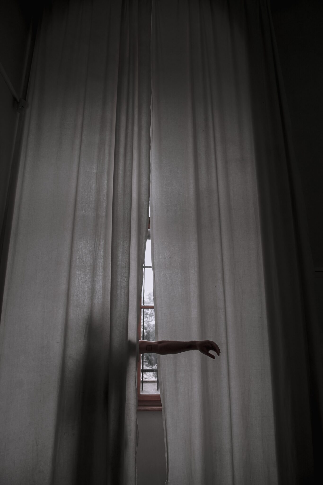 The silhouette of a person is seen behind curtains. Their arm is ticking out from the curtains. | What Helps Erectile Dysfunction - Passion by Kait
