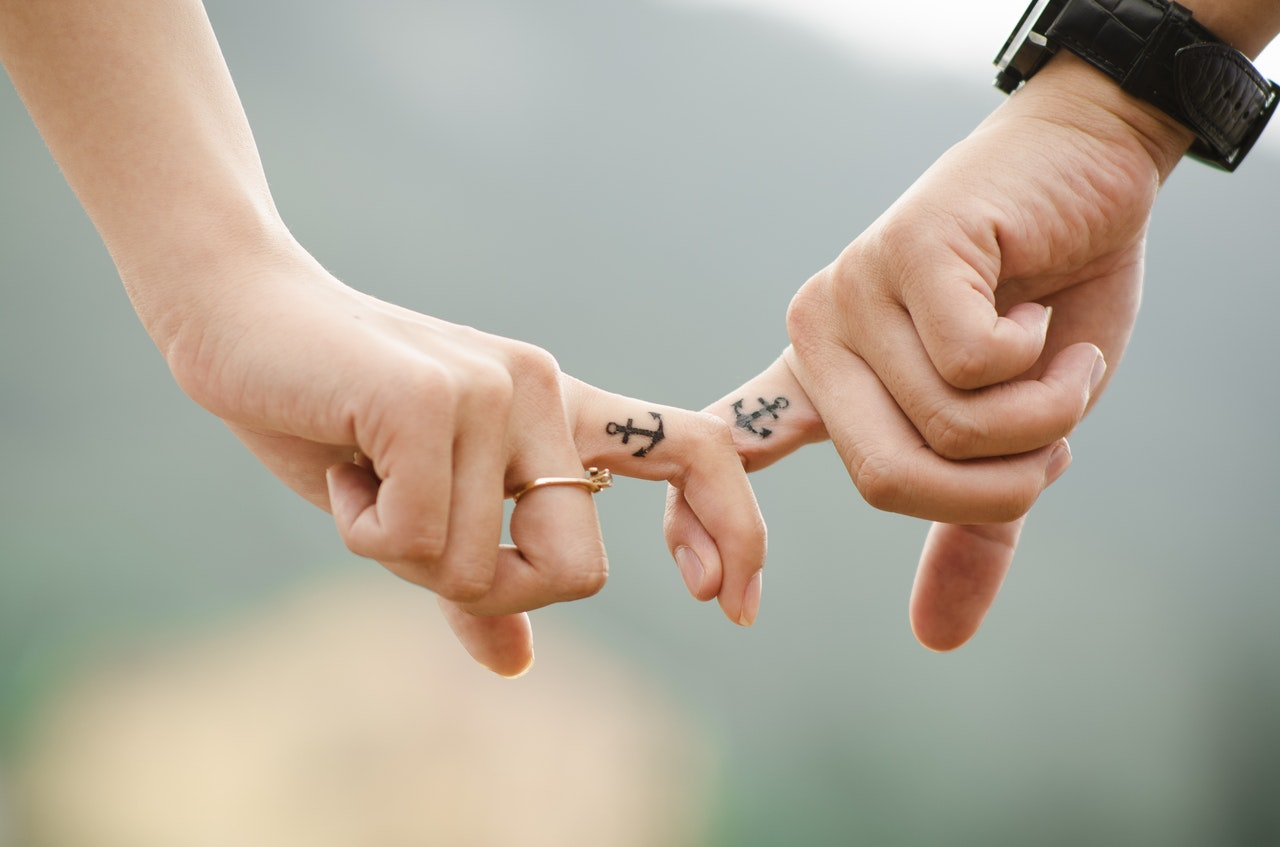 Two hands with the index finger of each hand intertwining and both index fingers have a tattoo of an anchor and one finger has a ring | Yes You Can! How to Have a Simultaneous Orgasm in 9 Steps | Passion by Kait