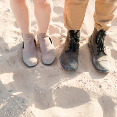 two people standing side by side on the sand one wearing light brown boots, one is wearing black boots