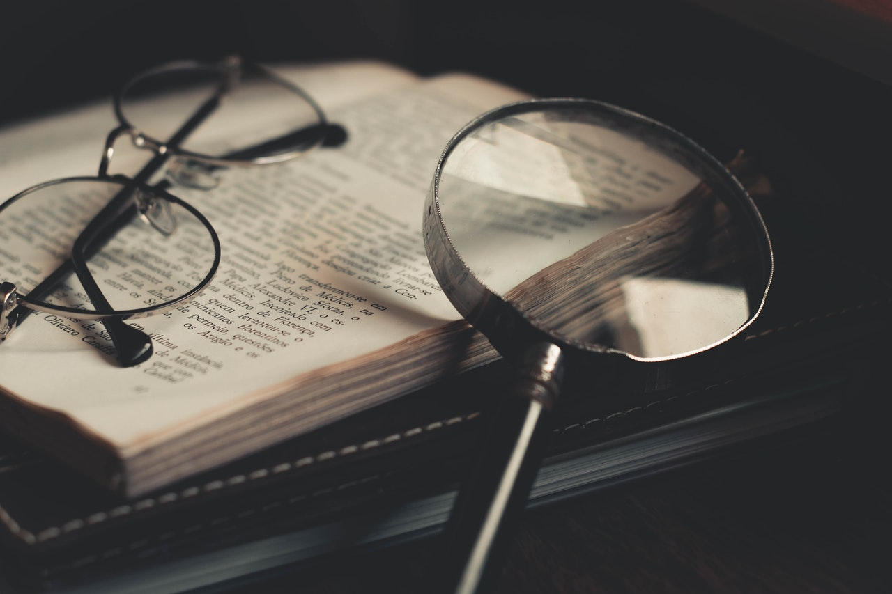 magnifying glass and reading glasses on top of a book | 8 Things You Didn't Learn in Sex Ed | Passion by Kait