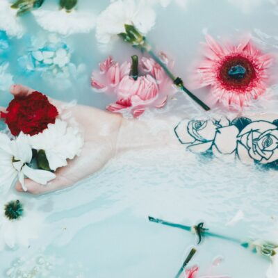 hand holding white, red and pink flowers in blue and white water