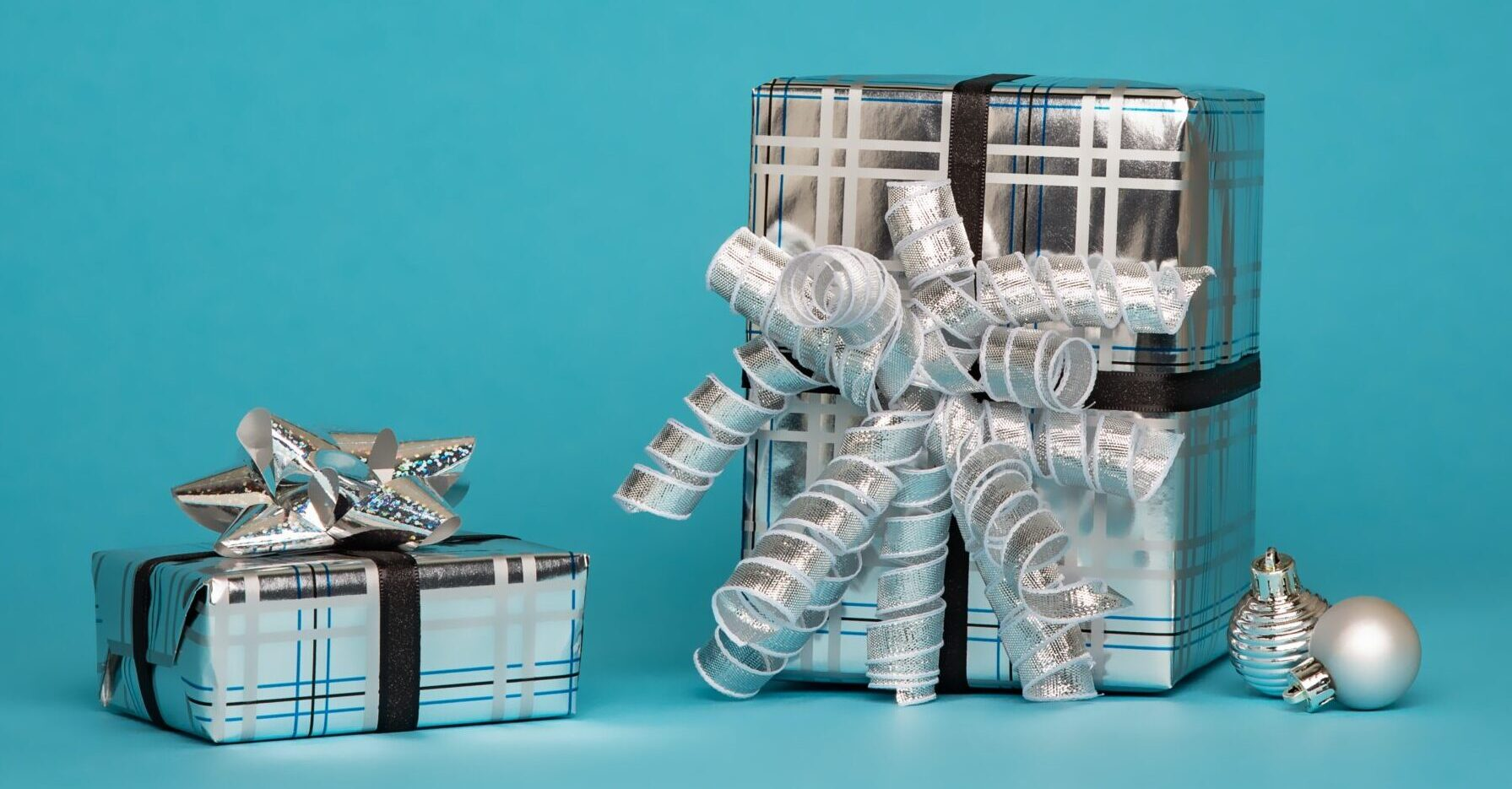 gifts wrapped in silver paper and silver ribbon on cyan background