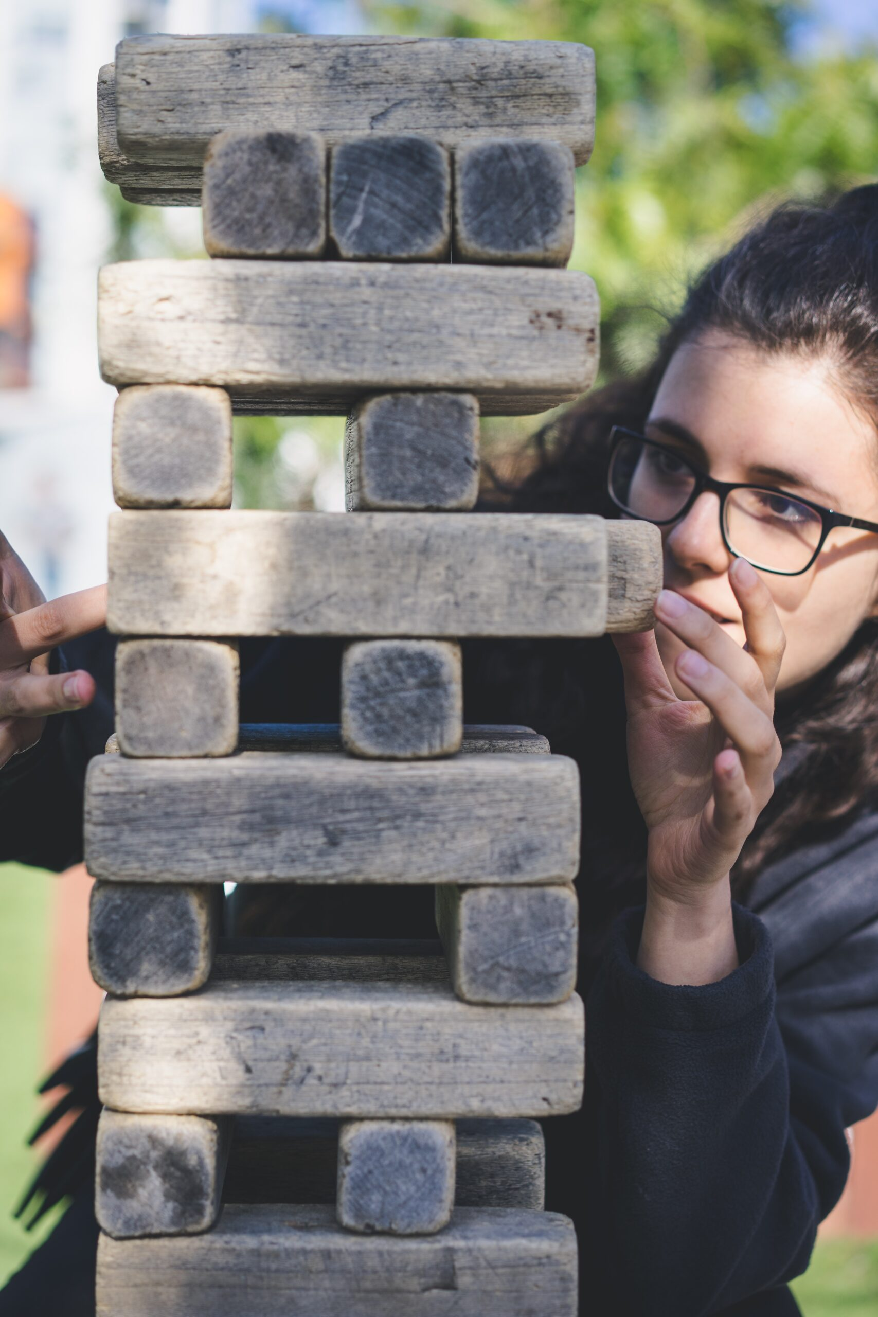 person with long brown hair with glasses concentrating on a large jenga style puzzle