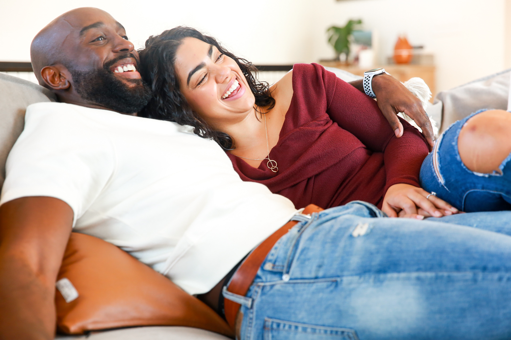 two people are lying together and embracing with one person putting their arm around the other and they are both smiling | The Best Sex Toys for Couples | Passion by Kait