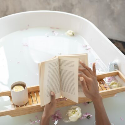 bathtub filled with milky colored water and flower petals, with 2 hands holding a book over a wooden rack holding a candle|AskKait: Which Books Have Characters That Use They/Them Pronouns?|Passion by Kait