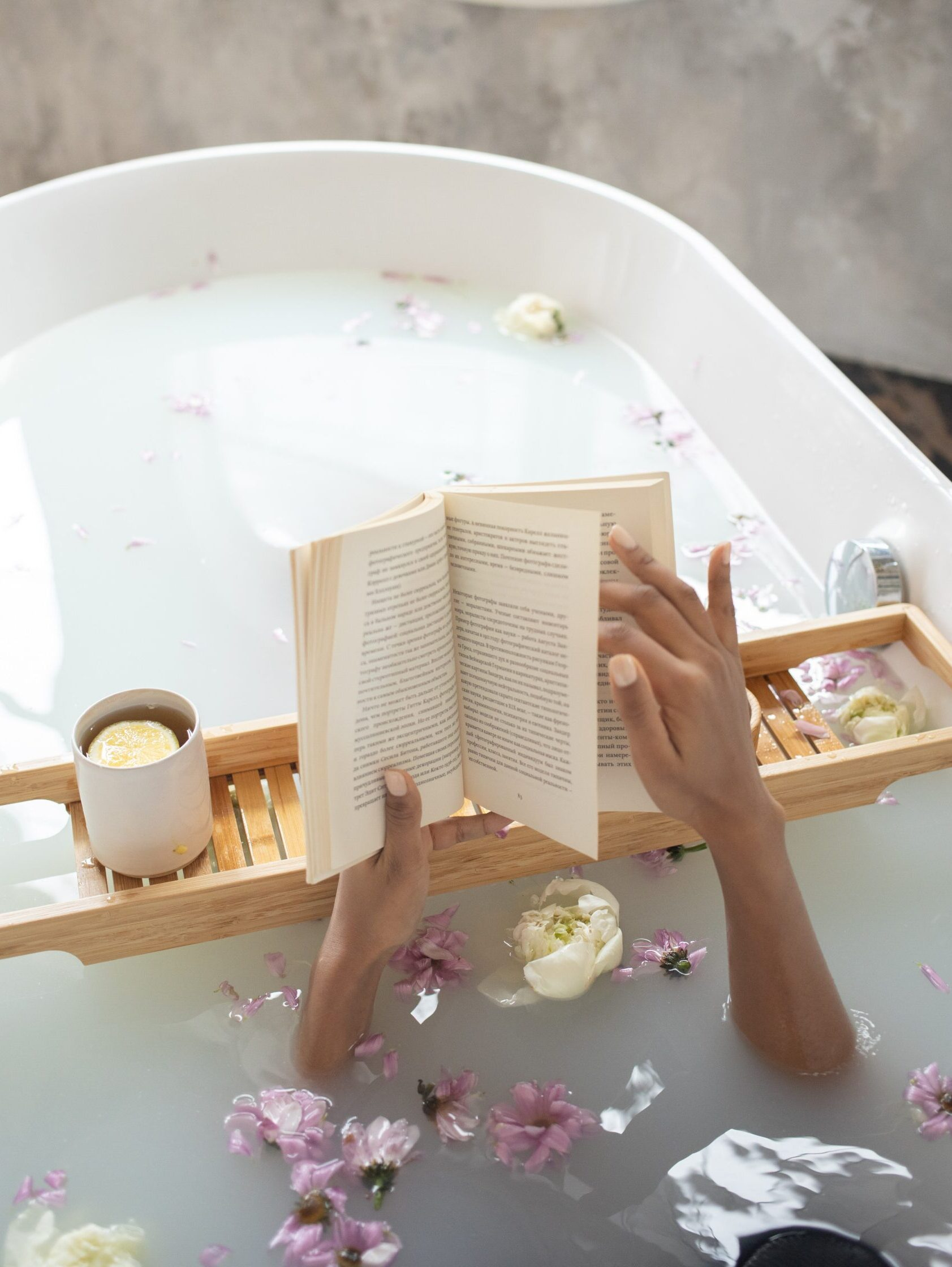 bathtub filled with milky colored water and flower petals, with 2 hands holding a book over a wooden rack holding a candle AskKait: Which Books Have Characters That Use They/Them Pronouns? Passion by Kait