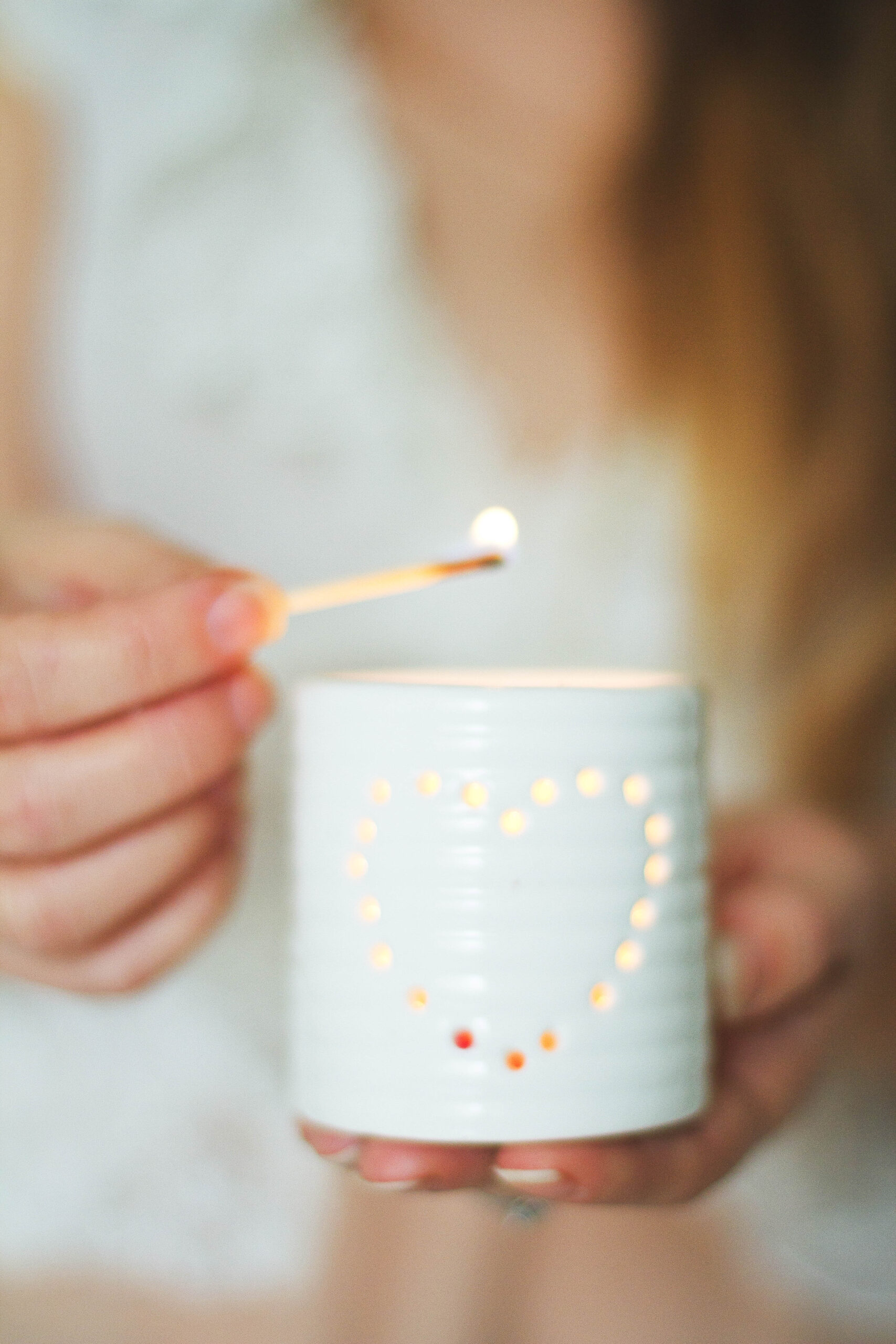 white candle holder with heart shaped motive with person in the background lighting candle with a match   9 Common Causes for Low Libido and How to Boost It   Passion By Kait